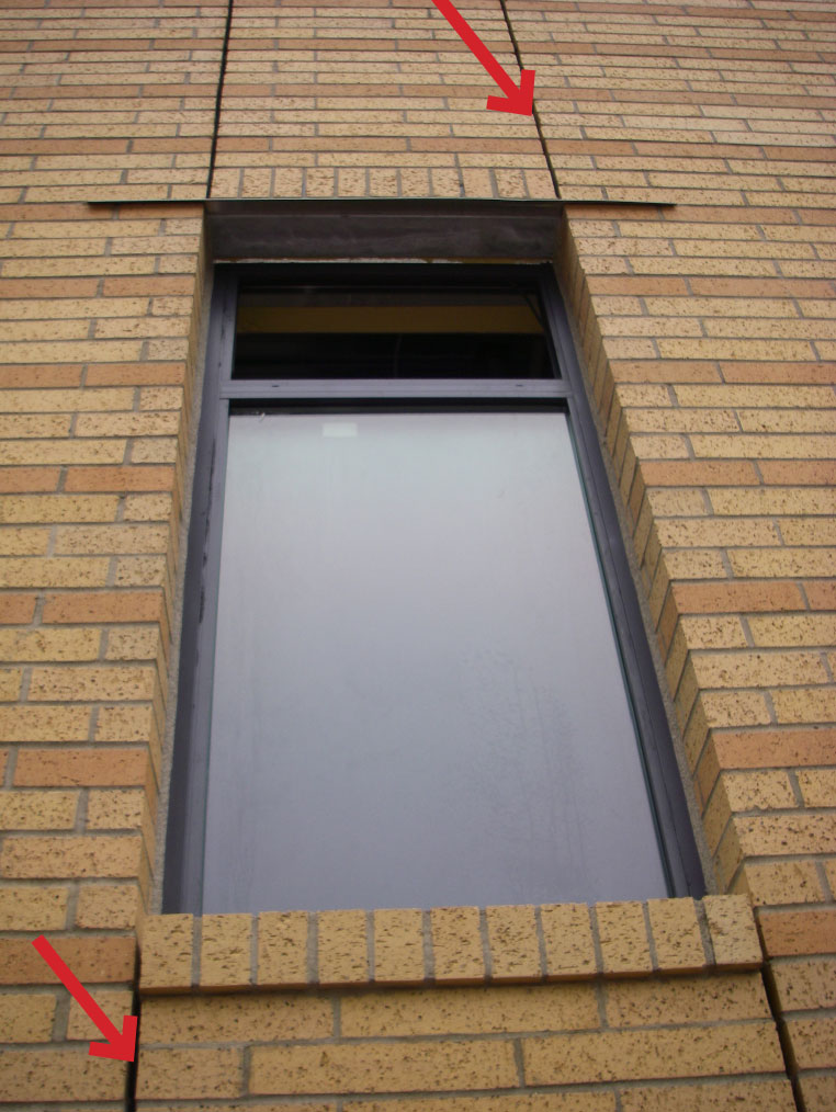 Fig. 1-18 Typical vertical brick expansion joint aligned with window jambs. Each joint continues the full height of the building and is awaiting backer rod and sealant joint installation.
