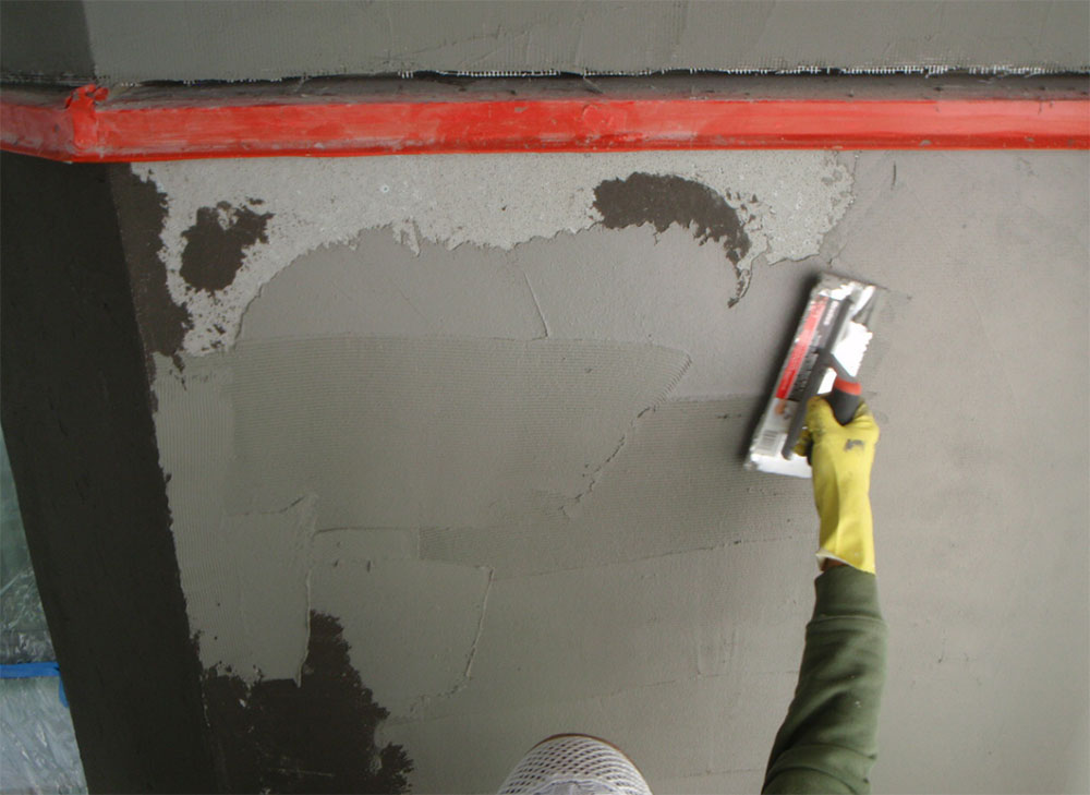 Fig. 6-13 Crack isolation membrane application over cement backer board. Cement board corners and fastener locations are treated prior to membrane application. A trowel-applied membrane is shown; membranes may also be fluid-applied.