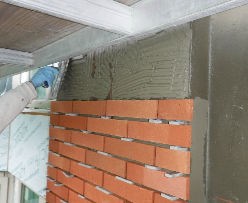 Fig. 7-14 Installation of masonry veneer over thinset adhesive mortar and crack isolation membrane.