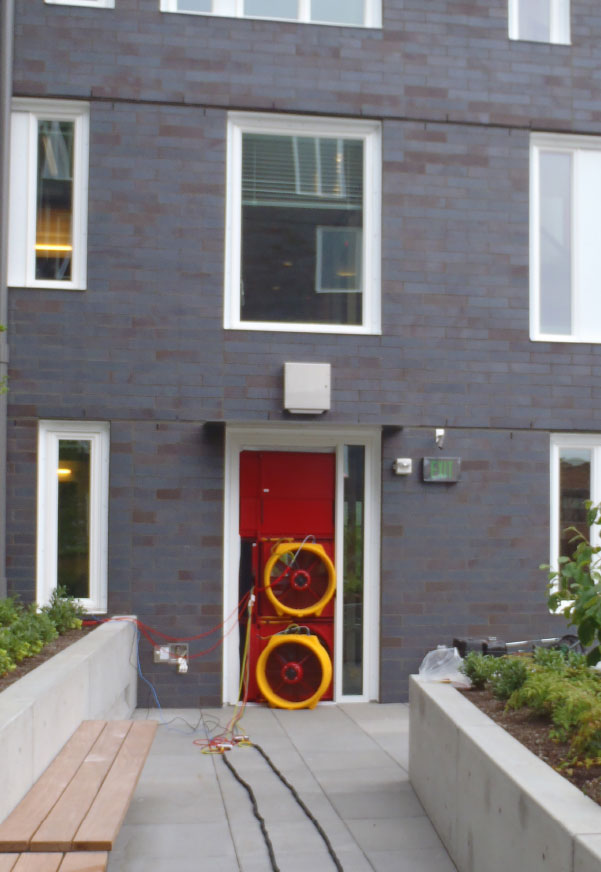 Fig. i-23 Blower door setup during whole-building air leakage testing of building with an anchored masonry veneer above-grade wall assembly.