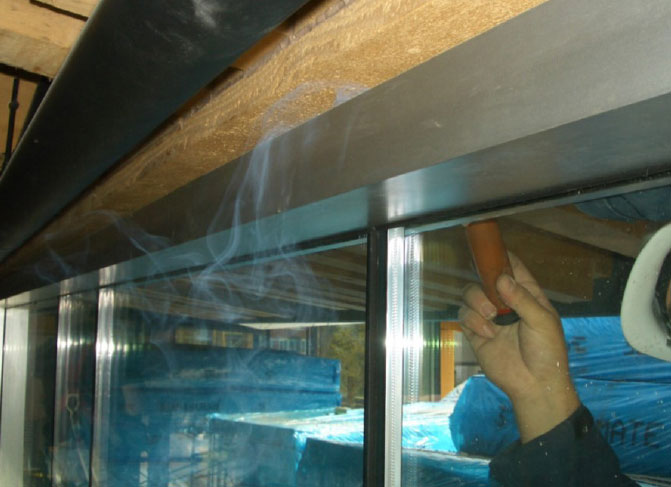 Fig. i-25 A smoke pencil is used to conduct diagnostic air leakage testing while a building is under positive air pressure. Smoke exits the building through a discontinuity at the head of the window rough opening.